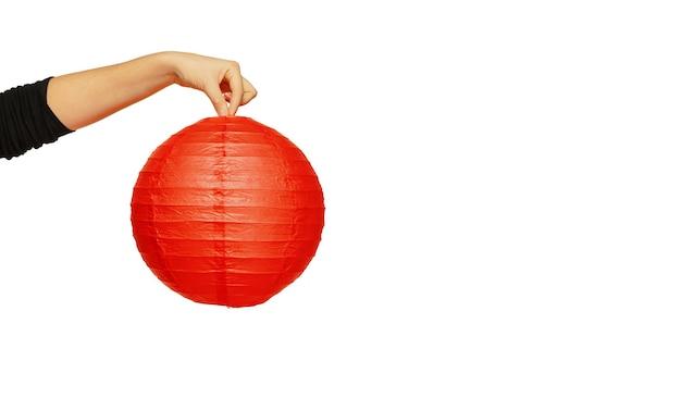 vrouwelijke hand met rode lantaarn geïsoleerd op een witte muur. viering, decoratie, vakantieconcept. copyspace voor uw advertentie. flyer, buitentent.