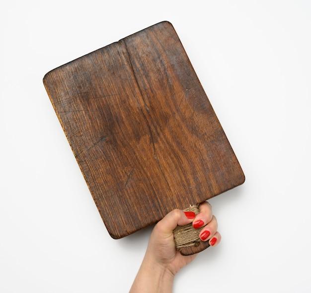 Vrouwelijke hand met rode manicure houdt lege oude vintage rechthoekige keuken snijplank op witte achtergrond