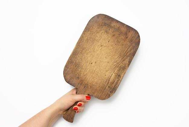 Vrouwelijke hand met rode manicure houdt lege oude vintage rechthoekige keuken snijplank vast