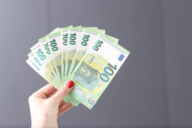 Vrouwelijke hand met rode manicure met veel euro-geldbankbiljetten close-up winnende loterij