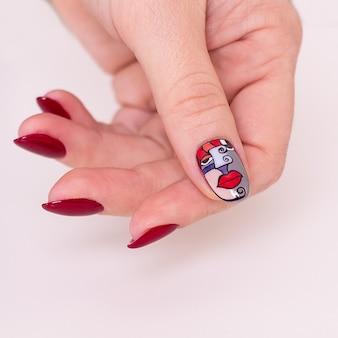 Vrouwelijke hand met rode manicurespijkers
