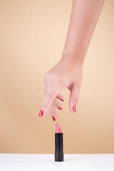 Vrouwelijke hand met rode vingernagels die lippenstift nemen