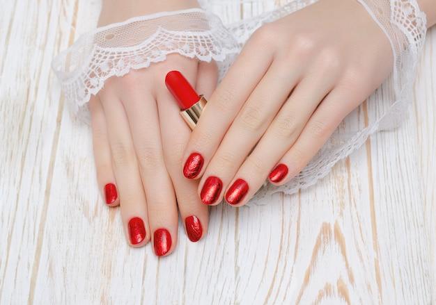 Vrouwelijke hand met rood spijkerontwerp die rode lippenstift houden.