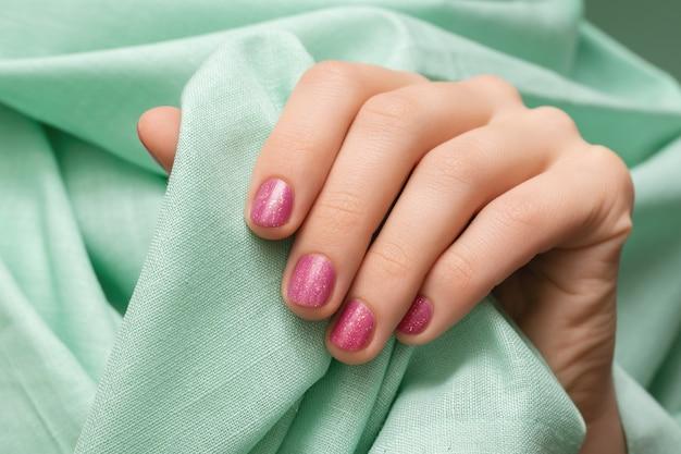 Vrouwelijke hand met roze glitter nagel ontwerp.