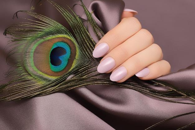 Vrouwelijke hand met roze nagel ontwerp met pauwenveer.