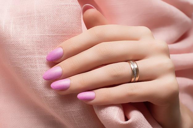 Vrouwelijke hand met roze spijkerontwerp op roze stoffenoppervlak.