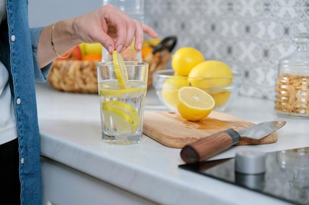 Vrouwelijke hand met schijfje citroen in keuken, met vers gemaakte drank bruisend water met citroen