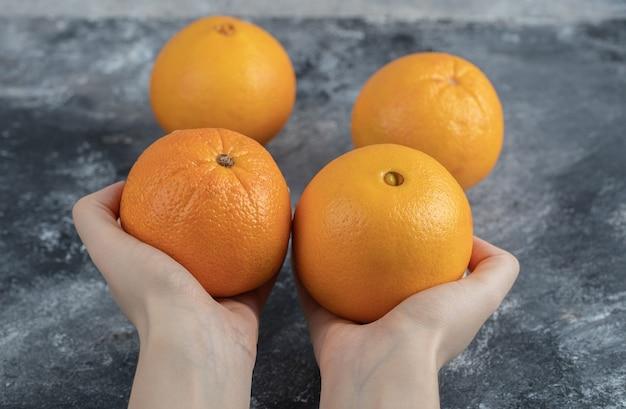 Vrouwelijke hand met sinaasappelen op marmeren tafel.