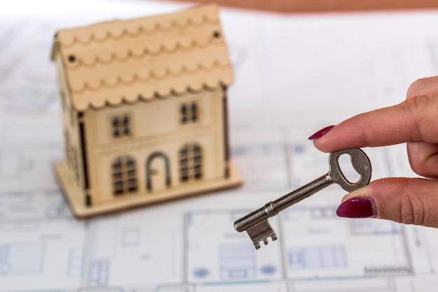 Vrouwelijke hand met sleutel en speelgoedhuis op plan