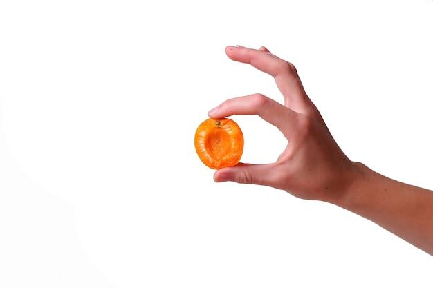 Vrouwelijke hand met smakelijke abrikoos op witte achtergrond. crème voor handen en behandeling of biologisch gezond voedselidee en concept