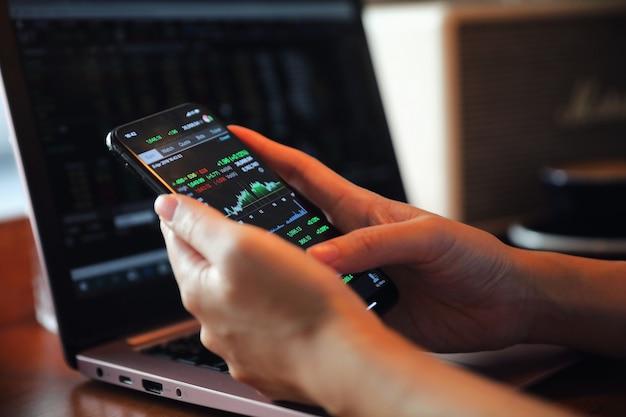 Vrouwelijke hand met smartphone handelend voorraad online in koffiewinkel, bedrijfsconcept
