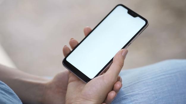 Vrouwelijke hand met smartphone met wit scherm. meisje met behulp van mobiele telefoon tijdens het wandelen in het najaar park.