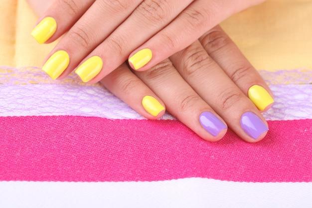 Vrouwelijke hand met stijlvolle kleurrijke nagels, op helder