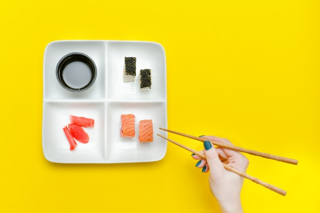 Vrouwelijke hand met stokjes en plaat met sushi op een gele achtergrond.