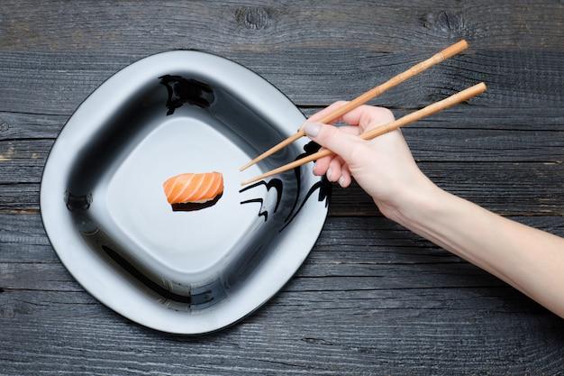 Vrouwelijke hand met stokjes en sushi. bovenaanzicht