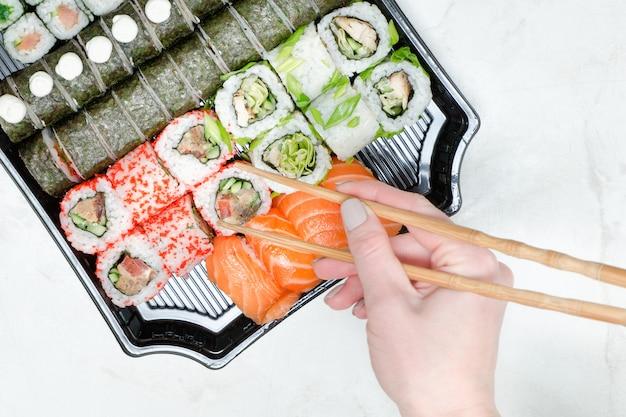 Vrouwelijke hand met stokjes en sushi set