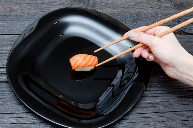 Vrouwelijke hand met stokjes en sushi