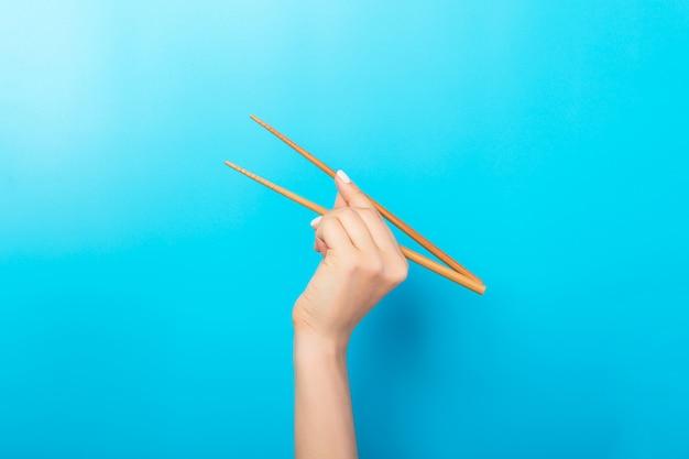 Vrouwelijke hand met stokjes op blauw. traditionele aziatische gerechten met lege ruimte voor uw ontwerp