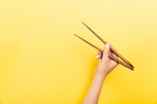Vrouwelijke hand met stokjes. traditioneel aziatisch eten