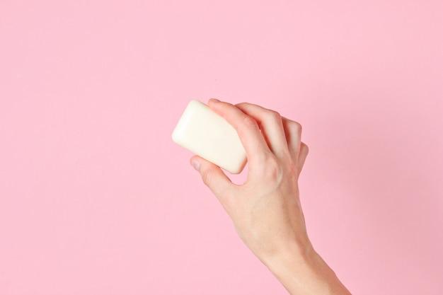 Vrouwelijke hand met stuk zeep tegen roze.