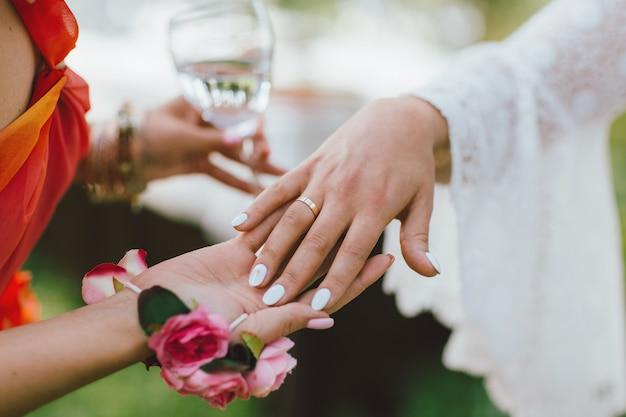 Vrouwelijke hand met trouwring, bruidsmeisjes