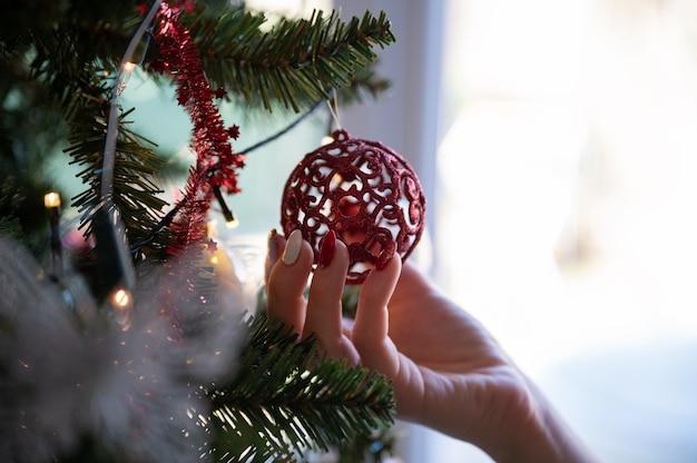 Vrouwelijke hand met vakantie manicure met glanzende rode kerstbal opknoping van een kerstboom met verlichting