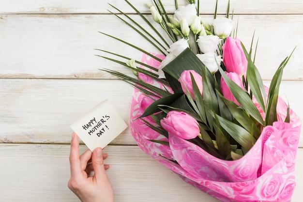 Vrouwelijke hand met vakantiekaart en boeket bloemen