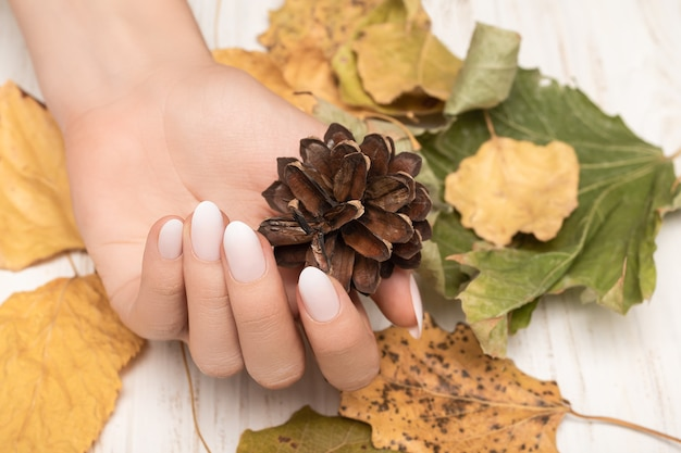 Vrouwelijke hand met wit nageldesign.