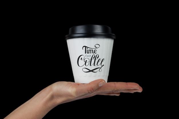 Vrouwelijke hand met witte koffiekopje op palm geïsoleerd op zwart met time for coffee hand belettering