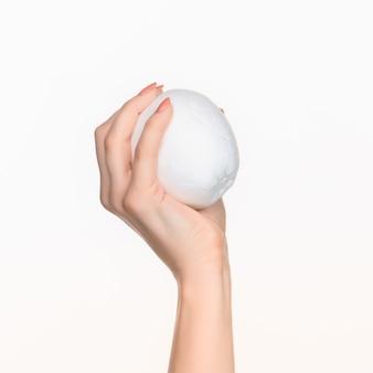 Vrouwelijke hand met witte lege piepschuim ovaal tegen de witte achtergrond met juiste schaduw