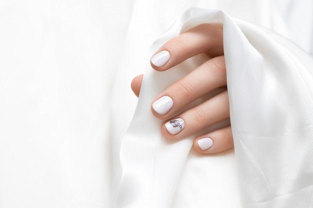 Vrouwelijke hand met witte paardebloem nagel ontwerp.