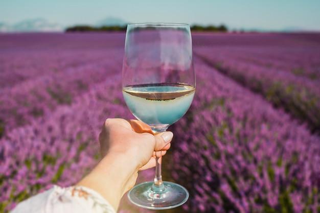 Vrouwelijke hand met witte wijnglas op een achtergrond van lavendelvelden in de provence, frankrijk