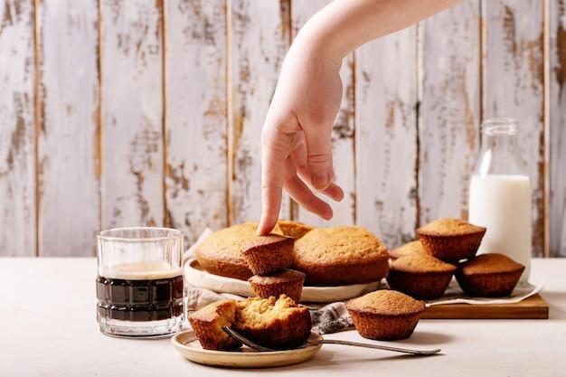 Vrouwelijke hand met zelfgemaakte muffins geserveerd met koffie op witte textuur achtergrond