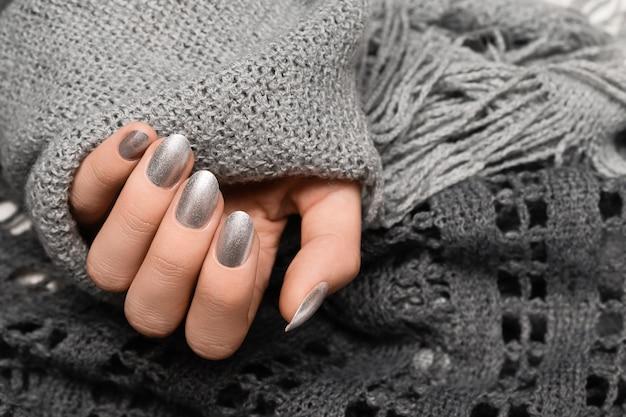 Vrouwelijke hand met zilveren spijkerontwerp. vrouw handen houden grijze wollen sjaal.
