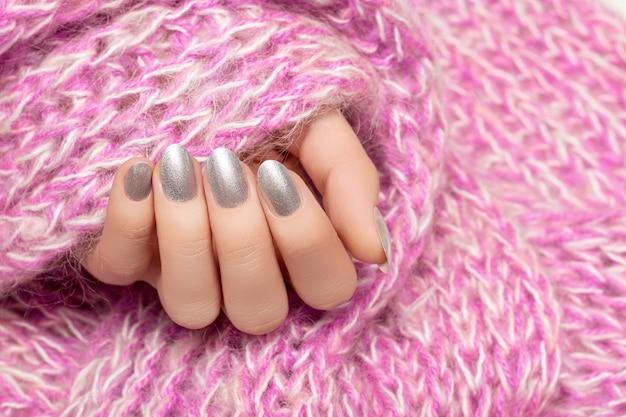 Vrouwelijke hand met zilveren spijkerontwerp. vrouw handen houden roze wollen sjaal.
