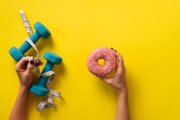 Vrouwelijke hand met zoete donut, meetlint, halters op gele achtergrond.