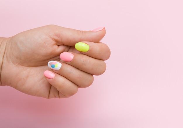 Vrouwelijke hand met zomermanicure met ijs op roze oppervlak
