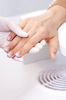 Vrouwelijke hand na manicure ter beschikking van manicuremeester bij nagelsalon