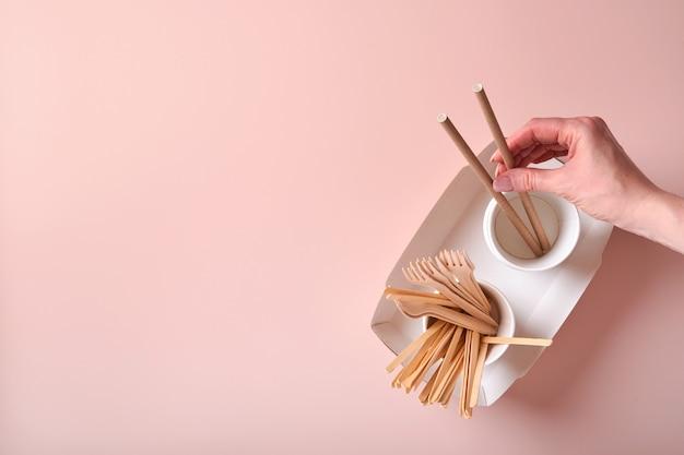 Vrouwelijke hand neemt cocktailrietjes, papieren bekers, borden, houten vorken, rietjes, fastfoodcontainers, houten bestek op roze achtergrond. eco ambachtelijk papier servies. recyclingconcept. bespotten.