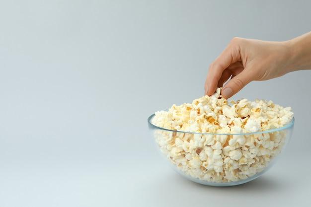Vrouwelijke hand neemt popcorn uit kom op lichtgrijze achtergrond.