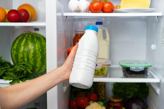 Vrouwelijke hand nemen fles melk uit een koelkast close-up