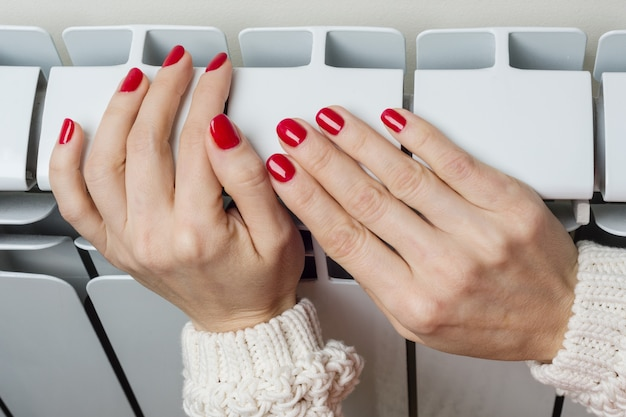 Vrouwelijke hand op de radiator