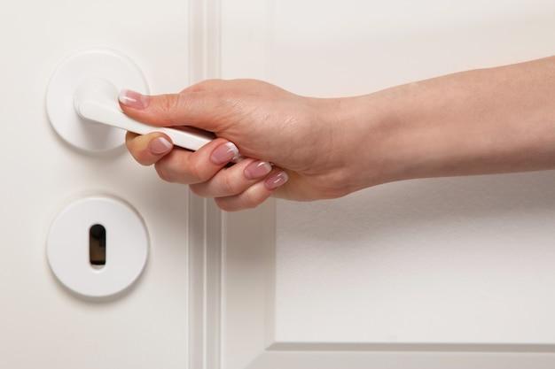 Vrouwelijke hand op deurklink
