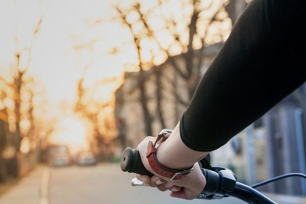 Vrouwelijke hand op het stuur van een fiets bij zonsondergang op straat. moderne gezonde levensstijl