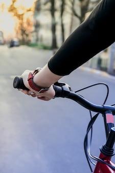 Vrouwelijke hand op het stuur van een fiets bij zonsondergang op straat. moderne sportlevensstijl
