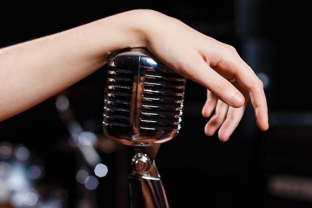 Vrouwelijke hand op retro microfoon close-up