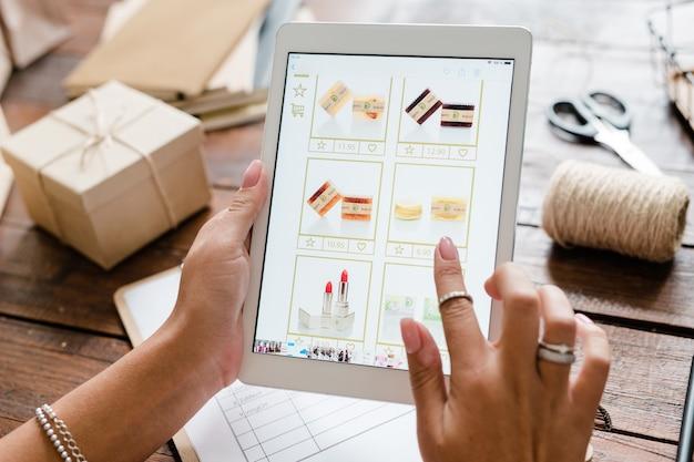 Vrouwelijke hand over touchpad-scherm gaat cosmetische producten kiezen tijdens het scrollen door de online winkel