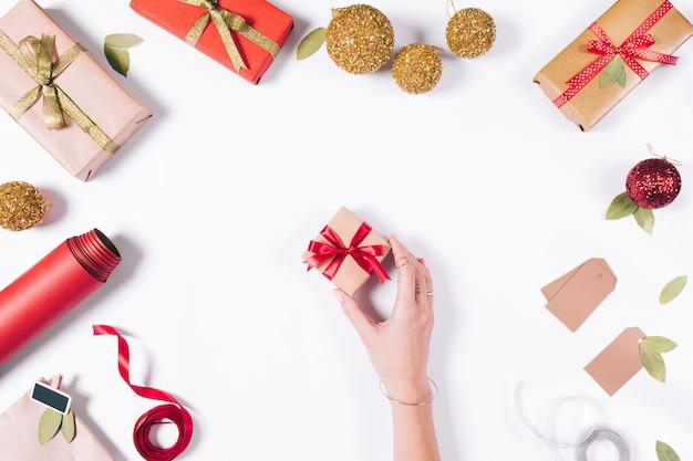 Vrouwelijke hand pakt een kleine doos met een geschenk op