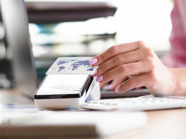 Vrouwelijke hand past contactloze betaalkaart toe. acquirer bank evalueert zaken. gebruik bankpas wereldwijd.