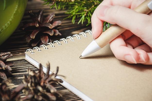 Vrouwelijke hand, pen, notitieboekje, op de achtergrond van kerstmisdecoratie
